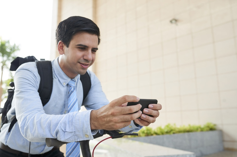 Smiling young handsome entrepreneur playing addictive game on smartphone