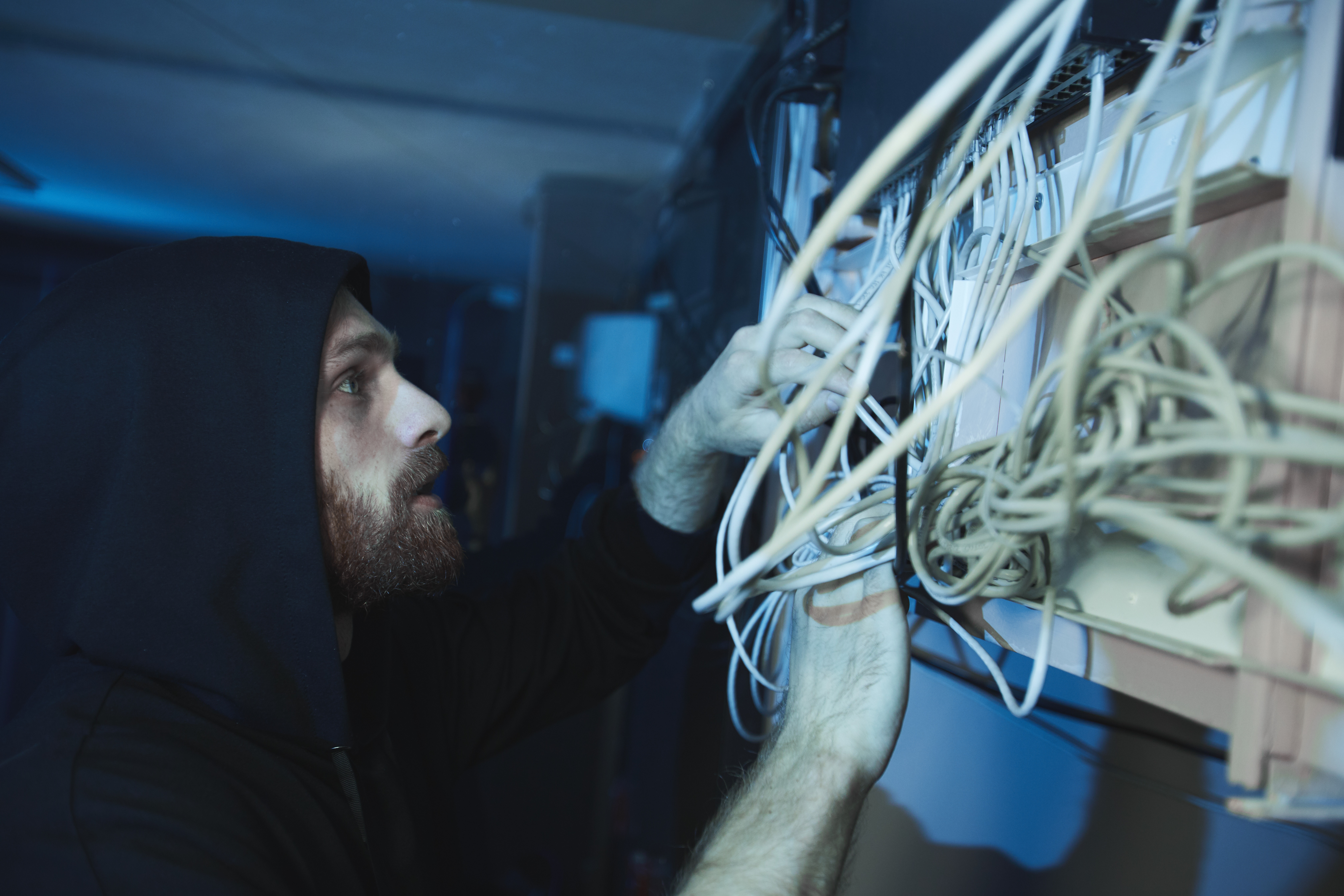 young man in hoodie checking cables of network server