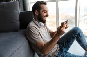 Optimistic young man play games by mobile phone