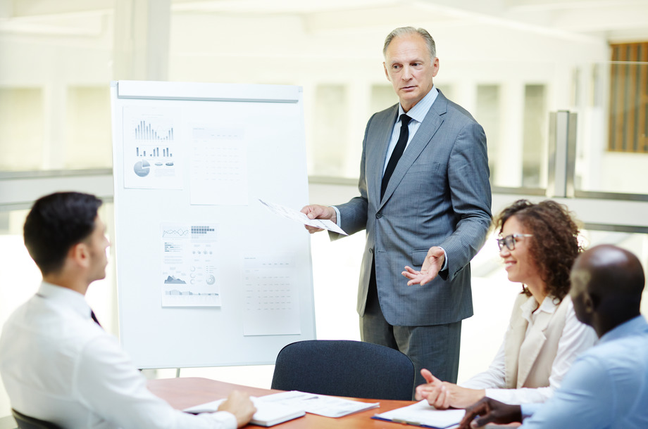 Confident senior business expert with paper standing by whiteboard